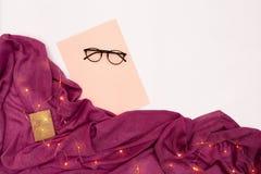 Vidrios negros, papel rosado con metas de los Años Nuevos Luces de la bufanda y de la Navidad en el fondo blanco Imágenes de archivo libres de regalías