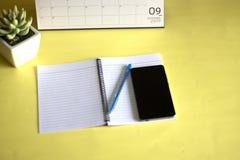 Vidrios, ordenador y cuadernos de la pluma colocados en un fondo amarillo Concepto de trabajo imagenes de archivo