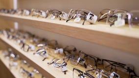 Vidrios para la vista Gafas de sol en una tienda Una colección de bastidores en el estante de una tienda almacen de metraje de vídeo