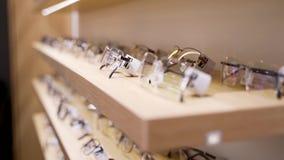 Vidrios para la vista Gafas de sol en una tienda Una colección de bastidores en el estante de una tienda metrajes