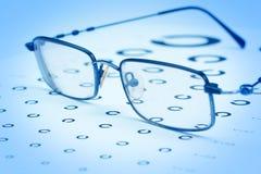 Vidrios para mejorar la visión en la tarjeta de la prueba. Fotografía de archivo