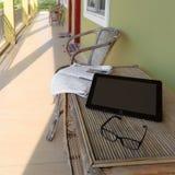 Vidrios, periódico y ordenador portátil en la tabla de madera en balcón del motel Imagenes de archivo