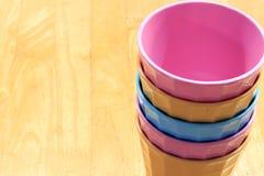 Vidrios plásticos coloridos en el fondo de madera Foto de archivo