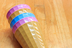 Vidrios plásticos coloridos en el fondo de madera Foto de archivo libre de regalías