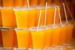 Vidrios plásticos con el zumo de naranja Fotografía de archivo