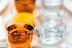 Vidrios plásticos con las bebidas en la tabla de banquete Fotografía de archivo