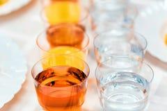 Vidrios plásticos con las bebidas en la tabla de banquete Imagenes de archivo