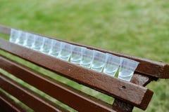 Vidrios plásticos en un banco Foto de archivo libre de regalías