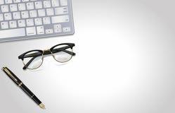 Vidrios, pluma, ordenador portátil - herramientas de la oficina en fondo gris claro Ilustración Visión desde la tapa Fotografía de archivo libre de regalías
