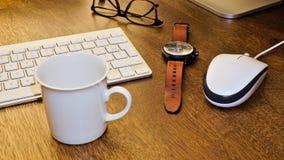 Vidrios, pluma, reloj, taza de café y teclado en una mesa de madera Imagenes de archivo