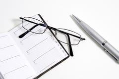 Vidrios, pluma y cuaderno Imagen de archivo