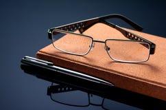 Vidrios, pluma y diario Accesorios del asunto Foto de archivo libre de regalías