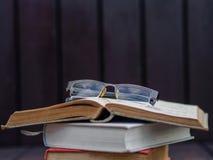 Vidrios puestos en la pila de libros Imagenes de archivo