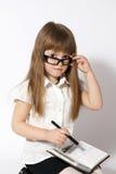 Vidrios que desgastan de la muchacha con el cuaderno Imagen de archivo libre de regalías