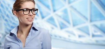 Vidrios que desgastan de la mujer en oficina Foto de archivo