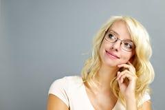Vidrios que desgastan de la mujer pensativa Imágenes de archivo libres de regalías