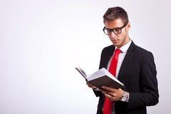 Vidrios que desgastan del estudiante y lectura de un libro de ley Imagen de archivo