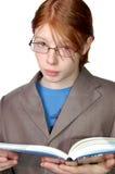 Vidrios que desgastan del muchacho serio con un libro Fotografía de archivo