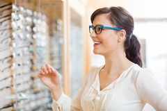 Vidrios que intentan de la mujer feliz en el óptico Store Imagenes de archivo