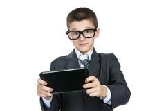 Vidrios que llevan chocados y sorprendidos del colegial del muchacho Muchacho elegante con una tableta en manos Foto de archivo
