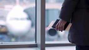 Vidrios que llevan de la chica joven o del adolescente, en una bufanda que mira un avión el aeropuerto, celebrando su pasaporte y almacen de video