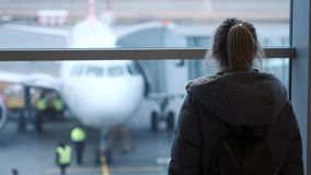 Vidrios que llevan de la chica joven o del adolescente, en una bufanda que mira un avión el aeropuerto, celebrando su pasaporte y metrajes