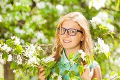 Vidrios que llevan de la muchacha del adolescente cerca de las flores blancas Fotos de archivo libres de regalías