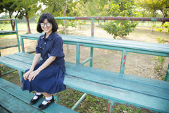 Vidrios que llevan de la muchacha que se sientan en el banco Foto de archivo