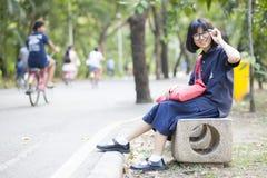 Vidrios que llevan de la muchacha que se sientan en un banco a lo largo del pasillo Fotos de archivo