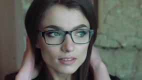 Vidrios que llevan de la mujer bonita y mirada a un lado lentamente almacen de video