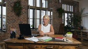 Vidrios que llevan de la mujer caucásica de mediana edad atractiva que se sientan en la tabla con el ordenador portátil durante d metrajes