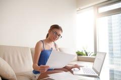Vidrios que llevan de la mujer joven que llevan a cabo el documento usando el ordenador portátil en el hom foto de archivo libre de regalías