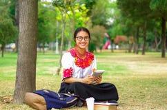 Vidrios que llevan de la mujer joven, falda andina tradicional y blusa con el collar rojo a juego, sentándose en hierba al lado d Imagen de archivo libre de regalías