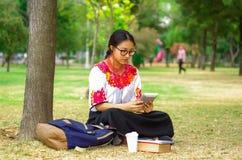 Vidrios que llevan de la mujer joven, falda andina tradicional y blusa con el collar rojo a juego, sentándose en hierba al lado d Imagen de archivo