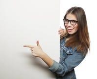 Vidrios que llevan de la mujer magnífica que señalan en un tablero mientras que suplente Fotos de archivo libres de regalías