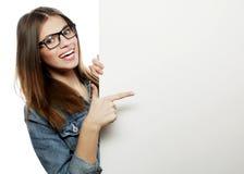 Vidrios que llevan de la mujer magnífica que señalan en un tablero mientras que suplente Foto de archivo libre de regalías