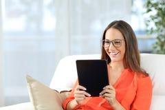 Vidrios que llevan de la mujer que leen una tableta Fotos de archivo libres de regalías