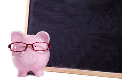Vidrios que llevan de Piggybank, pizarra en blanco, aislada, concepto de la educación universitaria, espacio de la copia Imagen de archivo