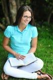 Vidrios que llevan del adolescente joven con el libro en un parque Imagen de archivo