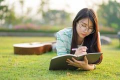 Vidrios que llevan del adolescente que se acuestan con la guitarra y los libros en el campo en la puesta del sol Imagen de archivo libre de regalías