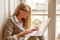 Vidrios que llevan del bussineswoman hermoso que se sientan en el alféizar con el ordenador portátil en sus manos Fotos de archivo