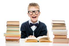 Vidrios que llevan del colegial con los libros para leer en una tabla en a Imagen de archivo