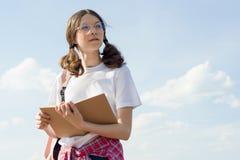 Vidrios que llevan del estudiante del adolescente con el libro de lectura de la mochila, fondo del cielo Imagenes de archivo