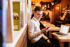 Vidrios que llevan del hombre feliz joven usando el teléfono móvil Fotografía de archivo libre de regalías