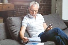 Vidrios que llevan del hombre usando en la tableta digital imagen de archivo libre de regalías