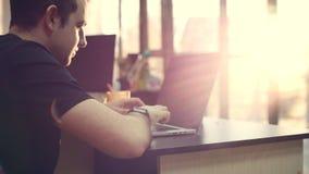 Vidrios que llevan jovenes del hombre de negocios con un reloj en sus manos, sentándose en una tabla, haciendo el trabajo en el o almacen de video