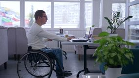 Vidrios que llevan perjudicados varón del Freelancer en el funcionamiento de la silla de ruedas en el ordenador portátil del telé almacen de video