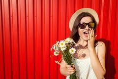 Vidrios que llevan y sombrero de la muchacha emocionada joven del inconformista con las flores contra fondo rojo Equipo del veran Imagen de archivo