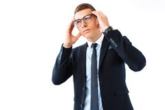Vidrios que llevan y traje del hombre de negocios pensativo, sosteniendo su hea fotos de archivo