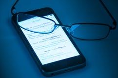 Vidrios que ponen en el teléfono celular con noticias en la pantalla Imagen de archivo libre de regalías